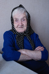 Portrait of an old woman with a scarf on her head.