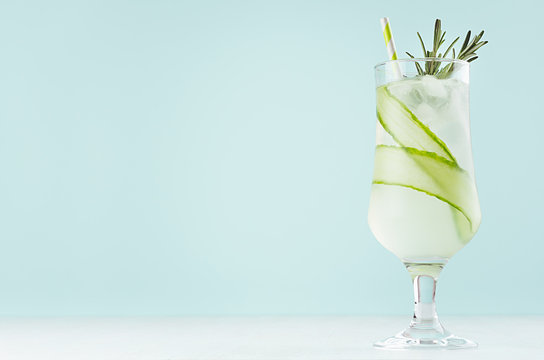 Summer fresh detox cucumber cocktail in wineglass with ice cubes, rosemary, straw on pastel mint color background, copy space.