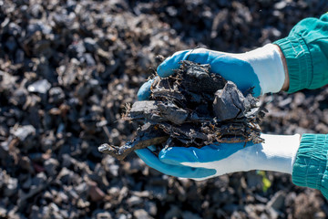 Close up of man holding pieces of shredded tires