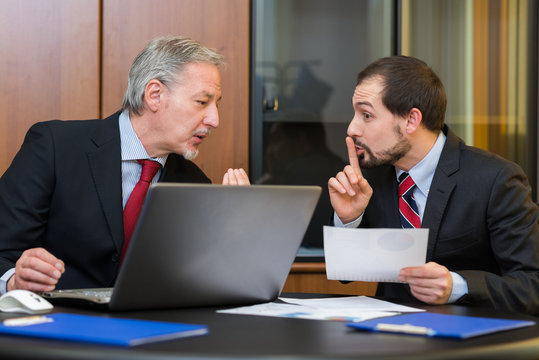Businessman asking his colleague to speak silently