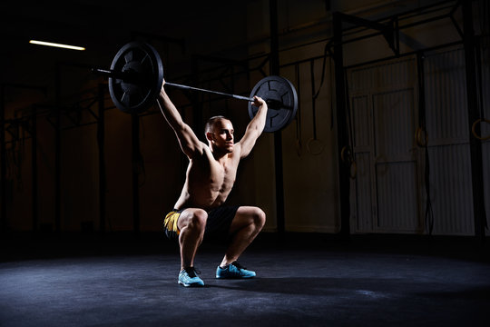 Athletic man training squats with barbells over head