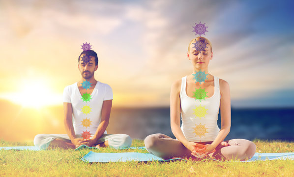 mindfulness, spirituality and outdoor yoga - couple meditating in lotus pose with seven chakra symbols over sea and sunlight background