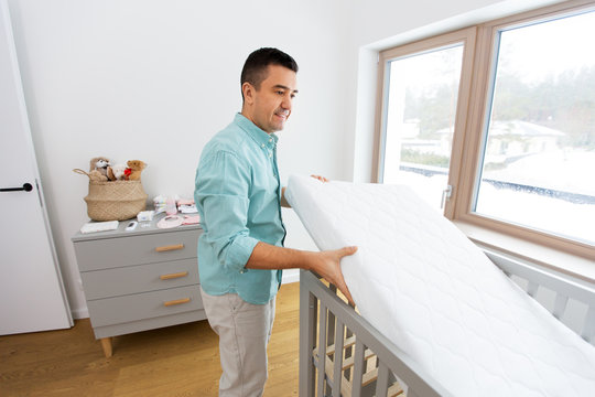parenthood, fatherhood and nursery concept - middle-aged father arranging baby bed with mattress at home