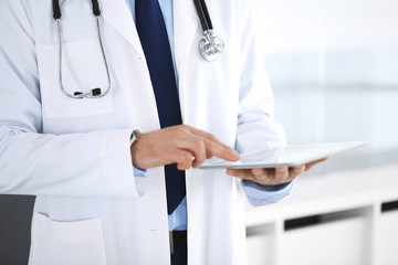 Doctor man using tablet computer for network research or virtual disease treatment, hands close-up. Perfect medical service in clinic. Modern  medicine, medic data and healthcare concepts