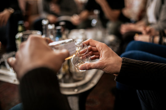 A close up shot of a man pouring whisky from a samlping bottle. Concept of fine alcohol, tasting of Japanese whisky. Master class and degustation.