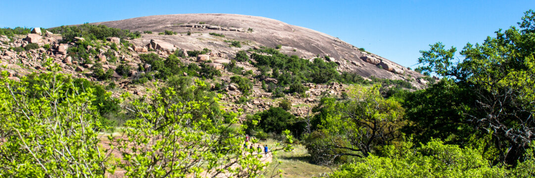 Panorama showing hikers on a trail at Enchanted Rock State Natural Area near Fredericksburg, Texas