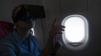 A woman in a virtual reality helmet, seating near a plane window