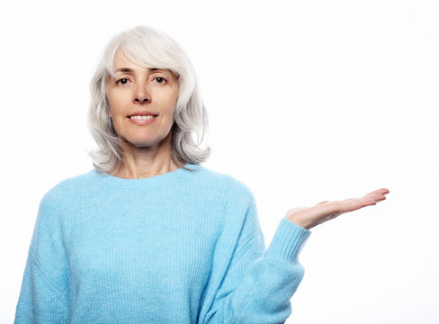 Lifestyle  and people concept: senior grey-haired woman showing your product