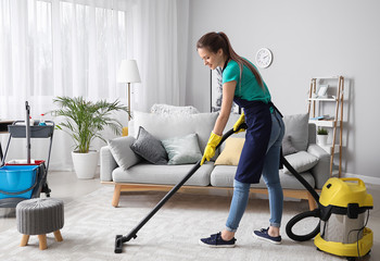 Female janitor with vacuum cleaner in room Wall mural