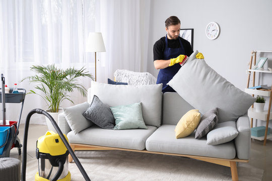 Male janitor cleaning sofa in room