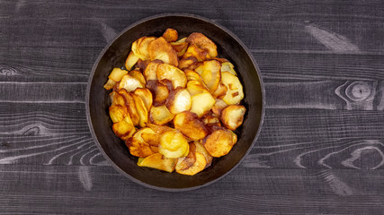 Fried homemade potato chips in a vintage antique cast-iron pan on a wooden rustic background.