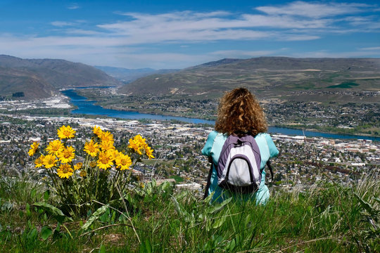 Woman with backpack sitting on the top of mountain enjoying scenic views of city and river. Spring wild flowers on hills. Wenatchee. Washington. United States