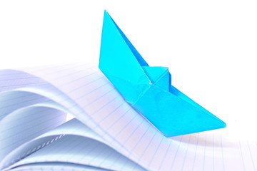 Origami blue paper boat rises to top on the sheets of a notebook bent like high stormy waves on white background. Isolated