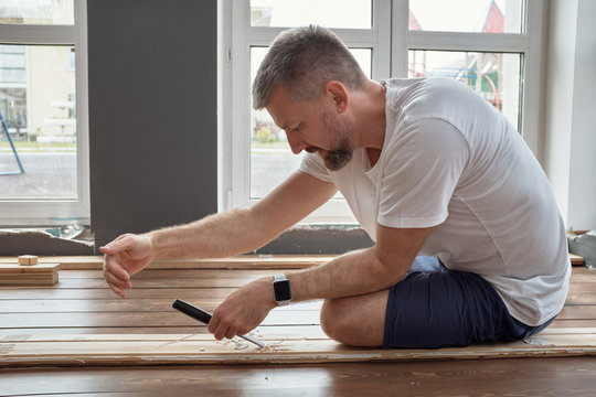 Man planing wooden plank for floor