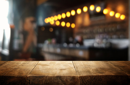 mage of wooden table in front of abstract blurred restaurant lights background