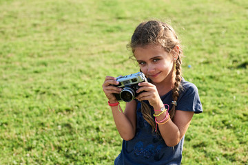 Small kid with film camera and braids looking at camera.