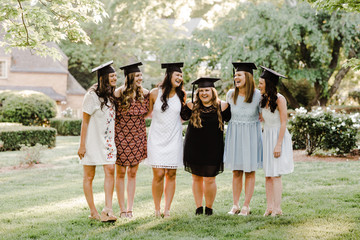 Female graduates in dresses and caps, no gowns