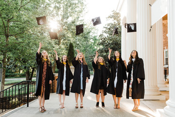 Female Graduates tossing caps into the air
