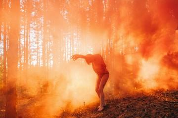 Silhouette of dancing woman in orange fog in sunset