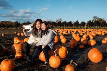 Asian Mother and Daughter Taking Selfie Picture During Pumpkin Patch