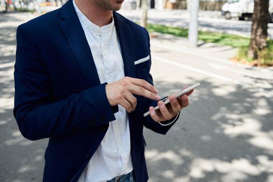 Entrepreneur checking data on the phone in the street.
