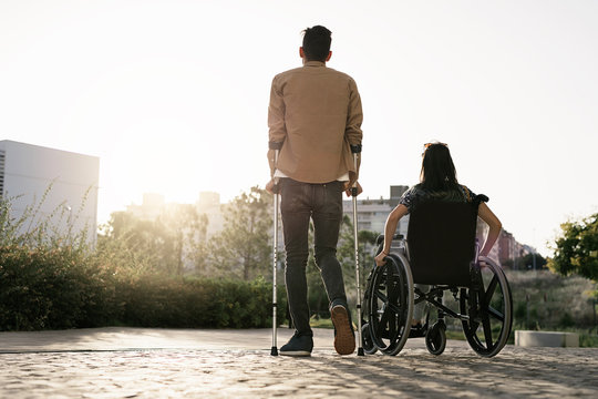 Back view of woman on wheelchair and her boyfriend using crutches