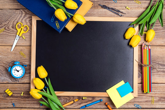 A chalkboard with school supplies and tulip flowers  on a rustic wooden table. Copy space for text.