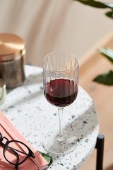 Close-up of red wine in glass on marble table.