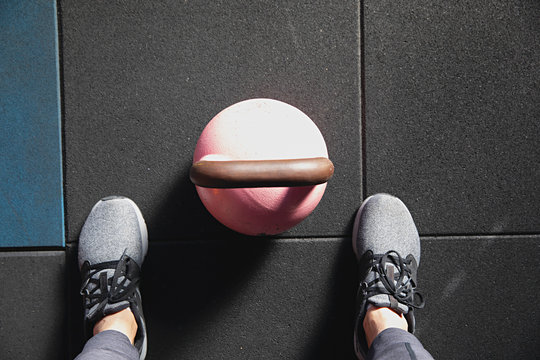 Colourful pink kettle bell weight with shadow at indoor gym