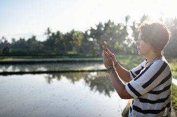 Woman taking picture of a rice paddy in the morning on her phone