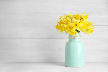 Bouquet of daffodils in vase on table against wooden background, space for text. Fresh spring flowers