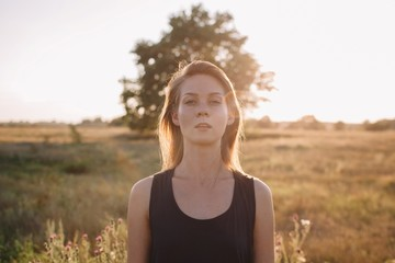 Portrait of young blond female in sunset light with rainbow sunbeam