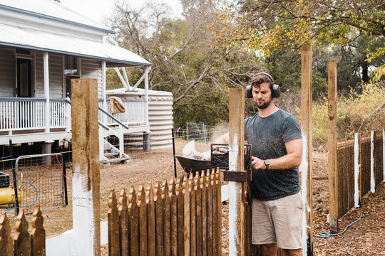 man cutting fence posts to size