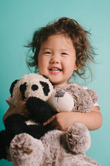 Little kid hugging stuffed animals