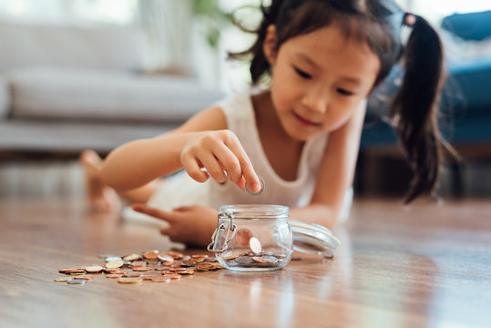 Adorable girl putting coins in jar