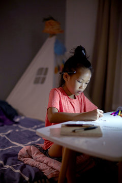 Asian little girl painting at home in the evening