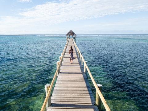 Woman on walking on a long wooden pier