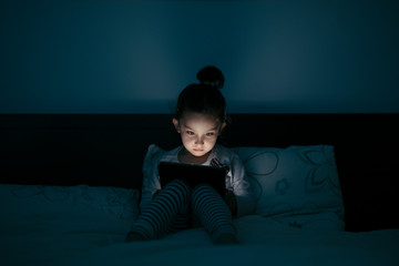 Girl with tablet In a dark room