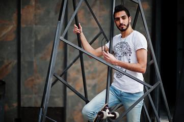 Street style arab man in eyeglasses with longboard posed inside metal pyramid construction.
