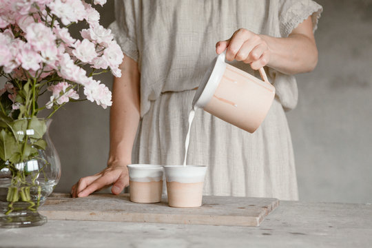 Woman pouring almond milk to cups