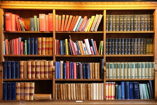 Books on a old wooden shelfs.