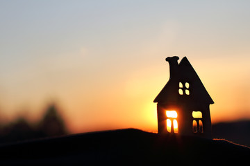 silhouette of a house with sun rays passing through the windows at sunset in the evening. living in a picturesque place