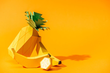 handmade paper pineapple, bananas and lemon on orange with copy space