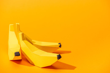 yellow paper bananas on orange with copy space