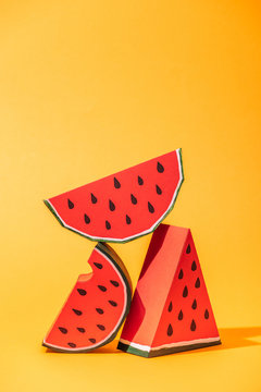 red paper watermelon slices on orange with copy space