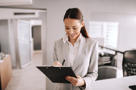 Smiling Caucasian successful businesswoman in formal wear standing at office in firm and writing on clipboard. The difference between who you are and who you want to be is what you do