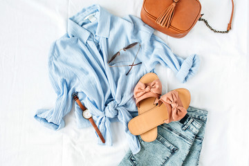 Feminine summer fashion composition with blouse, slippers, purse, sunglasses, watch, jean shorts on white background. Flat lay, top view minimalist clothes collage. Female fashion blog, social media. Wall mural