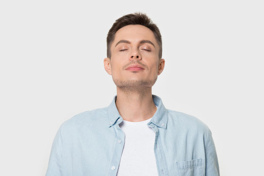 Calm Caucasian man breath deep enjoying pleasant smell