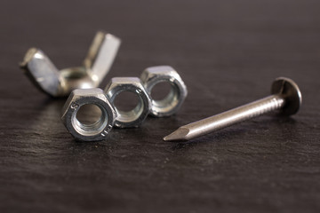 Group of five whole work item one metal wingnut, three locking nuts and one nail on grey stone