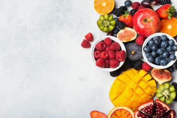Healthy raw rainbow fruits, mango papaya strawberries oranges passion fruits berries on oval serving plate on light kitchen top, top view, copy space, selective focus